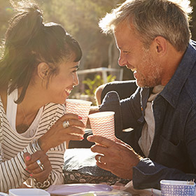 a couple laughing and enjoying a drink together