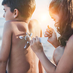 a sister applying suncream to her siblings back on the beach