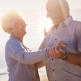 an older couple smiling and dancing together on a beach