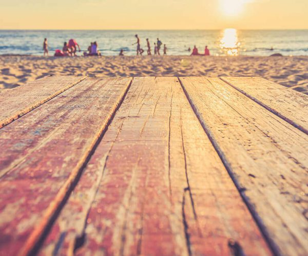 sandy wooden decking on the beach with people in the background